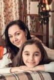 在一个沙发的两个俏丽的女孩、母亲和女儿选址在基督 免版税库存图片