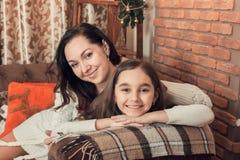 在一个沙发的两个微笑的女孩、母亲和女儿选址在克里斯 免版税库存照片