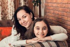 在一个沙发的两个愉快的女孩、母亲和女儿选址在Christm 免版税库存照片