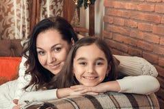 在一个沙发的两个美丽的女孩、母亲和女儿选址在Chr 库存图片