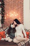 在一个沙发的两个逗人喜爱的女孩、母亲和女儿选址在Christma 免版税库存图片