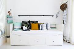 在一个沙发的五颜六色的枕头有白色砖墙的我 库存照片