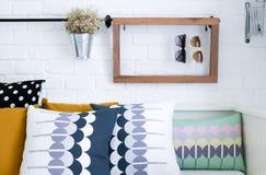 在一个沙发的五颜六色的枕头有白色砖墙的我 免版税库存照片
