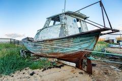 在一个沙滩放弃的一条老小船 免版税库存图片
