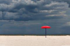 在一个沙滩的一把红色遮阳伞反对风雨如磐的天空背景 免版税库存图片