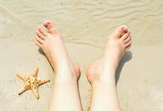 在一个沙滩的女性脚 免版税库存图片