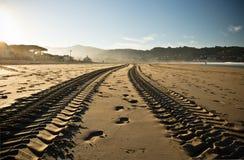 在一个沙滩的平直的引擎轮胎踪影轨道在hendaye 库存照片