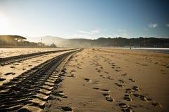 在一个沙滩的平直的引擎轮胎踪影轨道在hendaye 库存图片
