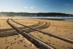 在一个沙滩的横渡的引擎轮胎踪影轨道在hendaye 库存图片