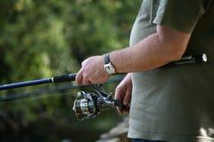 在一个河岸的人钓鱼一件T恤杉的在夏天在英国 免版税库存图片