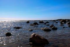 在一个沿海海滩的被日光照射了岩石 免版税图库摄影