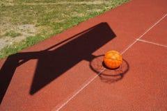 在一个法院的篮球与网的阴影 库存照片