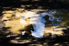 在一个泥泞的路水坑的反射剪影 免版税库存照片