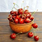 在一个泥罐的甜樱桃莓果在一张木桌上 o 免版税库存照片