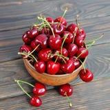 在一个泥罐的甜樱桃莓果在一张木桌上 免版税库存照片