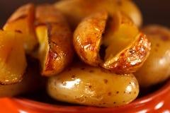在一个泥罐的被烘烤的土豆在木su的背景 免版税库存图片