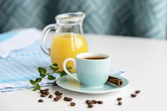 在一个浅兰的杯子的浓咖啡在一张白色桌上用橙汁 库存图片
