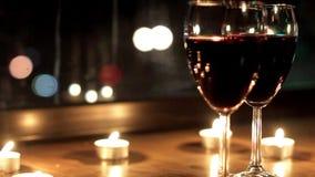 在一个浪漫晚上期间,发光在玻璃反射了用酒 股票录像