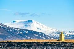 在一个海岛上的小灯塔有山的 库存照片