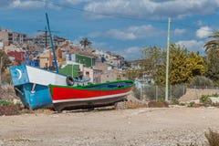 在一个海滩的一条红色小船与蓝天和棕榈树 免版税图库摄影