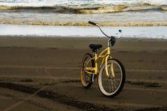 在一个海滩的一辆偏僻的自行车在与长滩华盛顿海洋的一个风雨如磐的秋天晚上期间在背景中 库存照片