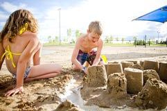 在一个海滩的孩子与沙子城堡 免版税库存照片