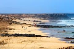 在一个海滩的未知的kitesurfers在El Cotillo村庄在费埃特文图拉岛海岛, Sp 免版税库存图片