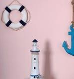 在一个海洋样式的构成 玩具圈子和船锚在桃红色颜色墙壁,灯塔立场上肩并肩垂悬, cas 库存图片