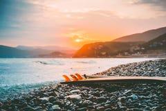 在一个海滩的冲浪板与温暖的日落或日出颜色 图库摄影