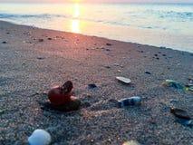 在一个海滩的日出与小石头 库存照片