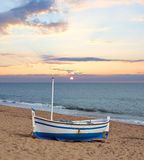 在一个海滩的木小船在日落 免版税库存照片