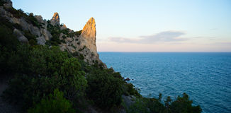 在一个海滩的海岸的日落与岩石的和在天际和蓝天的镇静水的A稀薄的橙色线与sunligh 图库摄影