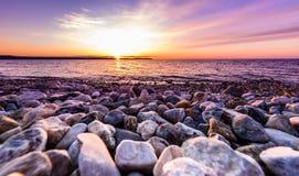 在一个海滩的石头与在海洋海的日落 免版税库存图片