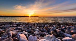 在一个海滩的石头与在海洋海的日落 免版税库存照片