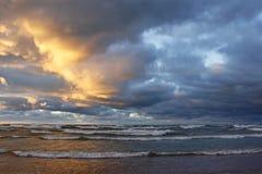 在一个海滩的暴风云在日落 免版税库存照片
