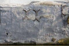 在一个涂灰泥的砖墙上的铁抽疯 免版税库存照片