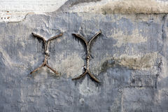 在一个涂灰泥的砖墙上的铁抽疯 库存图片