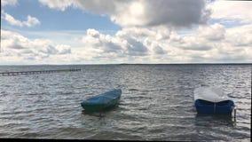 在一个淡水湖的晴朗的天气 在波浪岩石小船和筏上 在蓝天醉汉云彩 股票视频
