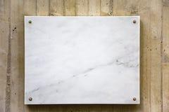 在一个混凝土墙上的白大理石委员会 图库摄影