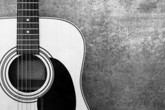 在一个混凝土墙特写镜头的背景的声学吉他,单色 免版税图库摄影