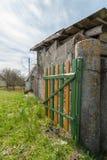在一个混凝土桩的农村木小门在谷仓和多云蓝天的背景 免版税库存照片