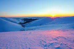 在一个清楚的冬日,从雪谷搽粉与雪,可以是被看见的美丽如画的积雪的山小山 库存照片
