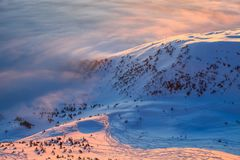 在一个清楚的冬日,从雪谷搽粉与雪,可以是被看见的美丽如画的积雪的山小山 库存图片