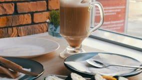 在一个清楚的玻璃杯子的咖啡拿铁在时髦的咖啡馆的寿司卷旁边 股票视频