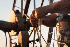 在一个渔船的日出有一个捕鱼网的到海里 拿着一个捕鱼网的老渔夫的手 免版税图库摄影