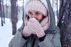 在一个温暖的冬天包裹的模型穿衣,喝在col的茶 图库摄影