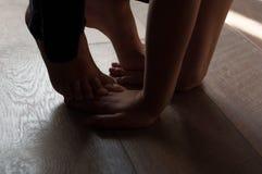 在一个温暖的木地板上的腿 免版税图库摄影