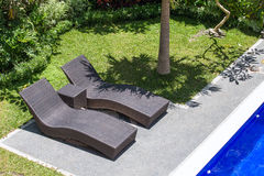 在一个游泳池旁边的两张海滩睡椅在一个热带庭院里 免版税库存照片