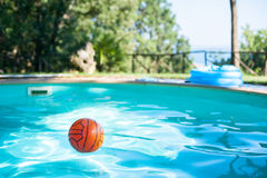 在一个游泳池的红色球在绿色庭院里 图库摄影
