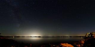在一个湖上的夜空有大城市光的在反面的 库存照片